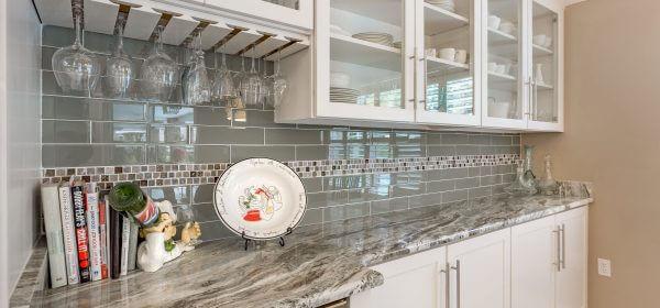 Custom Shaker cabinets with glass panels, granite countertops, and glass tile backsplash