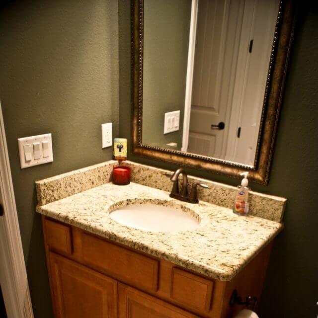 Custom bathroom cabinetry with granite countertop and backsplash