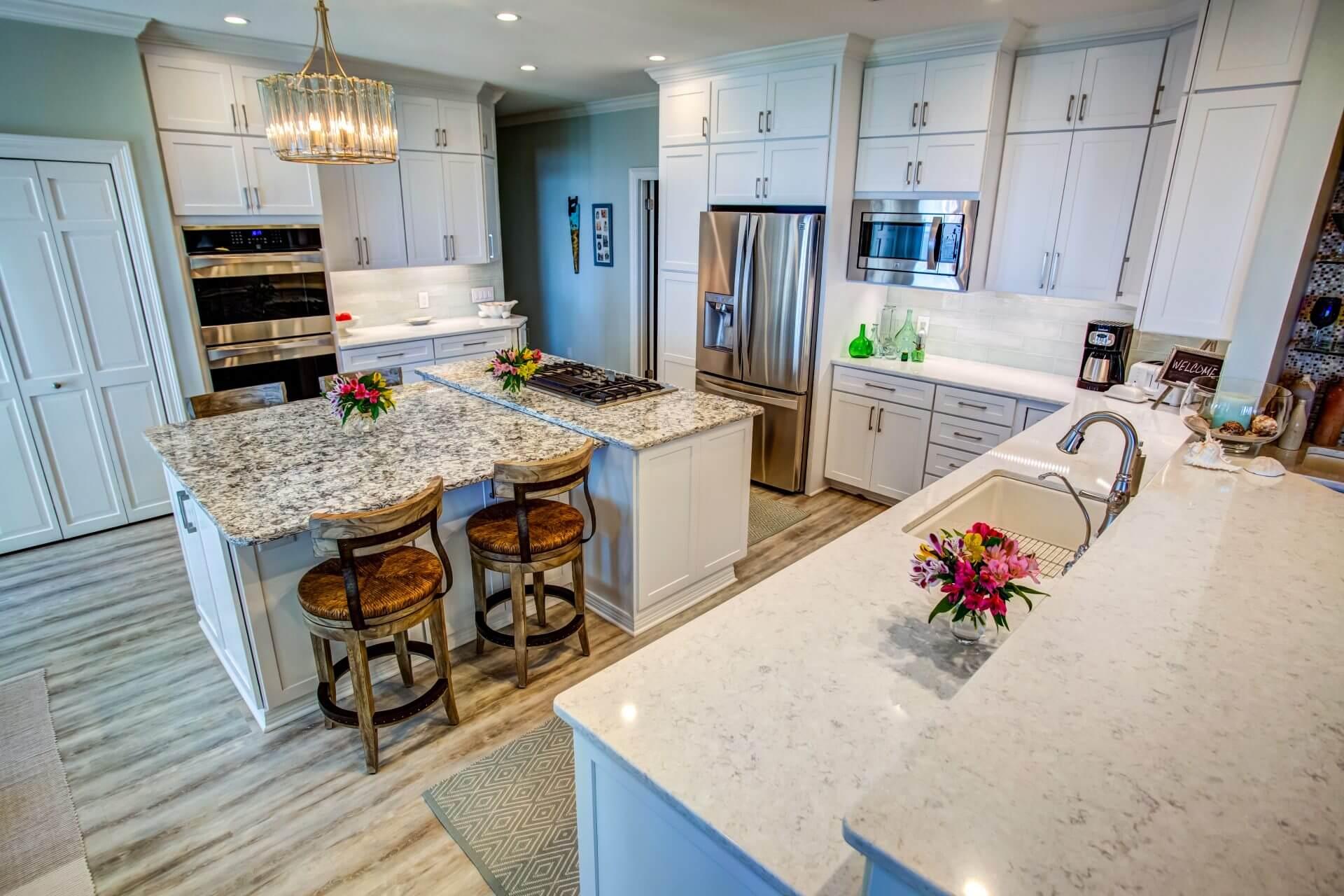 Sleek modern kitchen with stacked Shaker cabinets, quartz countertops and glass subway tile backsplash